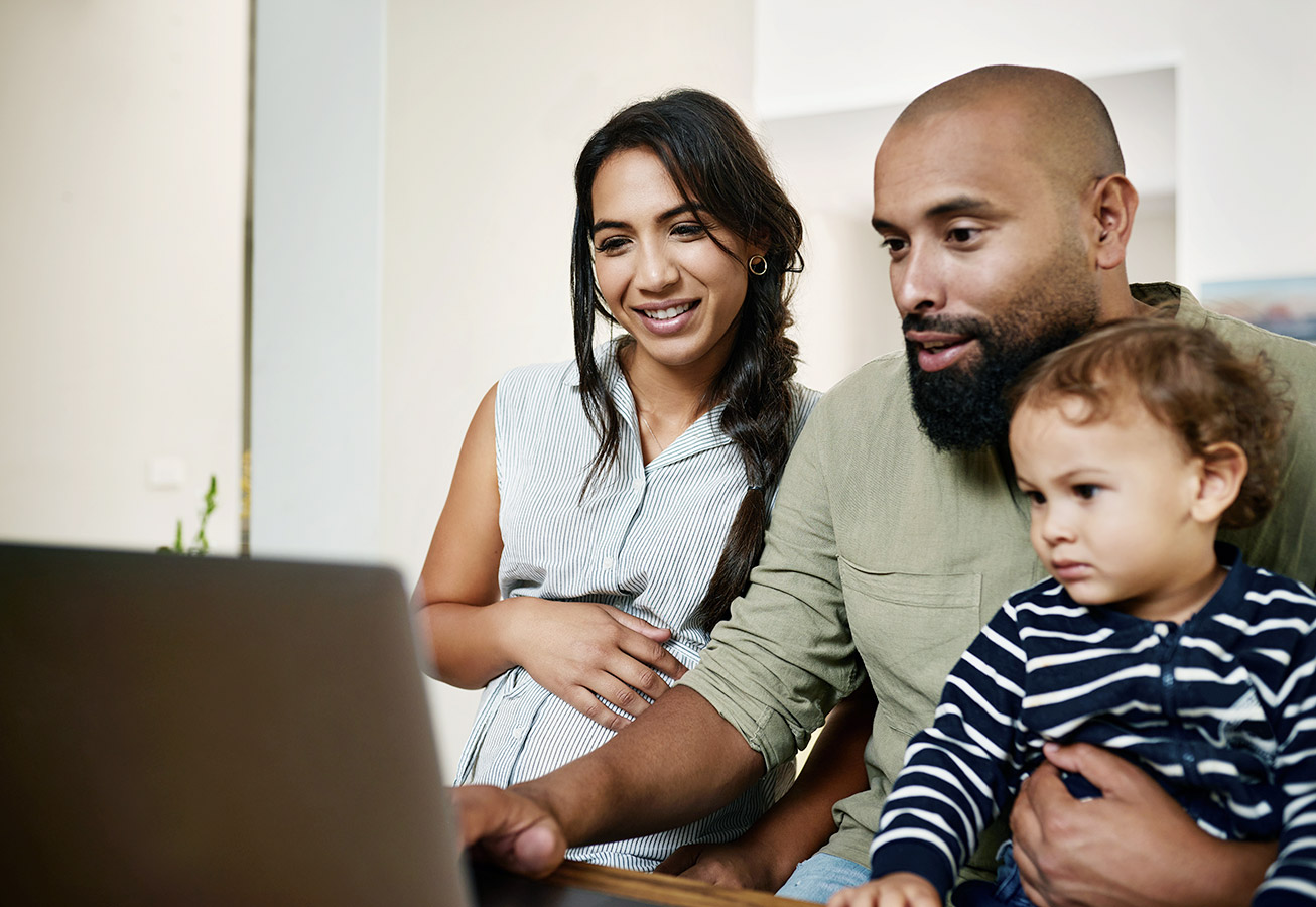 pregnant woman with husband and son looking at laptop