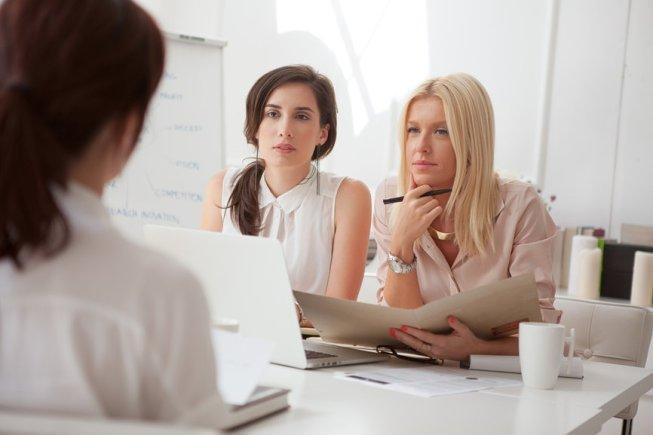 Two businesswomen interviewing a job candidate.