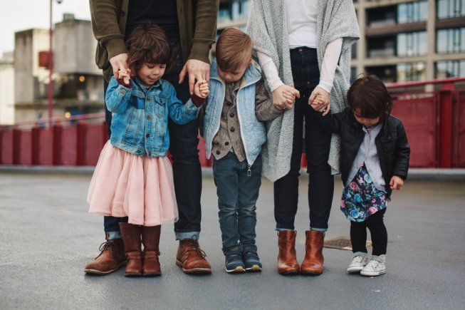 Family of five standing together - kids and feet only