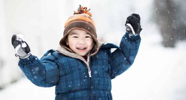 An Asian boy playing in the snow during winter
