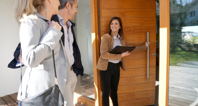 Real,Estate,Agent,Inviting,Couple,To,Enter,House,For,Visit