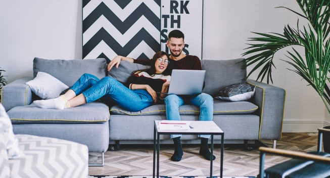 Young marriage resting on comfortable couch and watching funny movie on modern laptop device using wireless home internet.Couple in love doing shopping online together on digital netbook in apartment