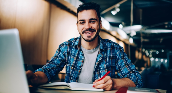 Portrait,Of,Cheerful,Male,Student,Enjoying,Learning,In,Coworking,Office