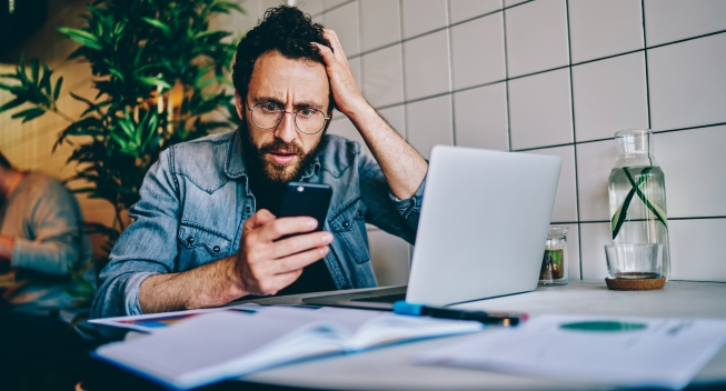 Stressful,Bearded,Young,Man,Received,Shocked,Sms,Message,On,Smartphone