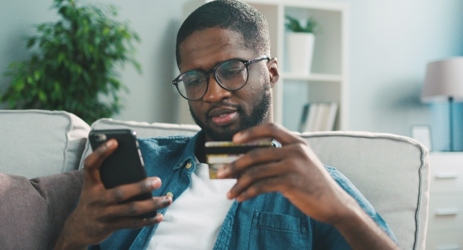 African,Young,Man,In,Glasses,Shopping,Online,With,Credit,Card