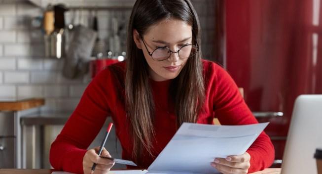 Indoor,Shot,Of,Woman,Financier,In,Optical,Glasses,Checks,Bank