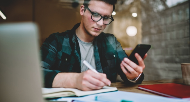 Pensive,Male,Student,In,Eyewear,Writing,Information,In,Notebook,Holding