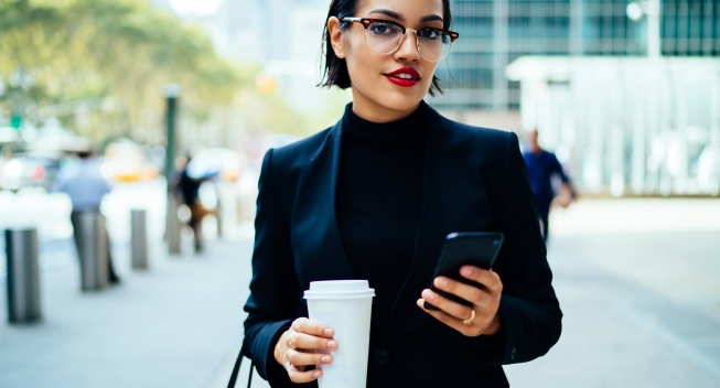 Smiling,Young,Businesswoman,In,Classy,Suit,Holding,Smartphone,And,Cup