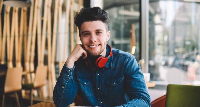 Half,Length,Portrait,Of,Cheerful,Bearded,Guy,Sitting,At,Cafe