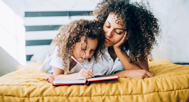 Careful,Daughter,Writing,In,Notebook,Lying,With,Curly,Haired,Female
