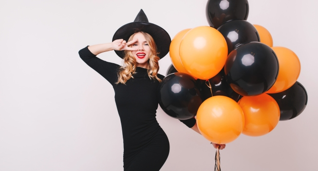 Attractive,Witch,Dancing,With,Hand,Up,,Holding,Helium,Party,Balloons.