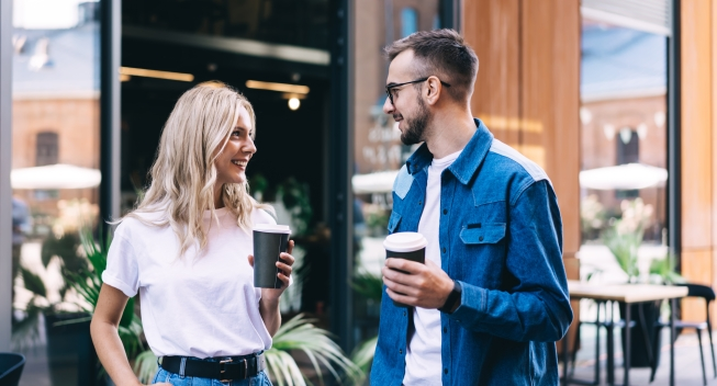 Positive,Young,Couple,With,Takeaway,Coffee,Enjoying,Conversation,While,Toothy