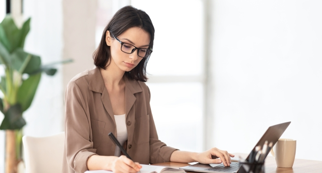 Note,Taking.,Portrait,Of,Female,Student,Using,Laptop,And,Writing