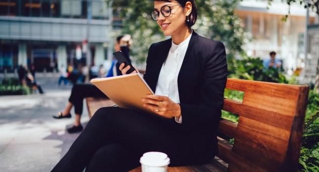 Cheerful,Businesswoman,In,Formal,Wear,And,Eyewear,Sitting,On,Bench