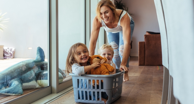Happy,Young,Mother,Pushing,Children,Sitting,In,Laundry,Basket.,Mother