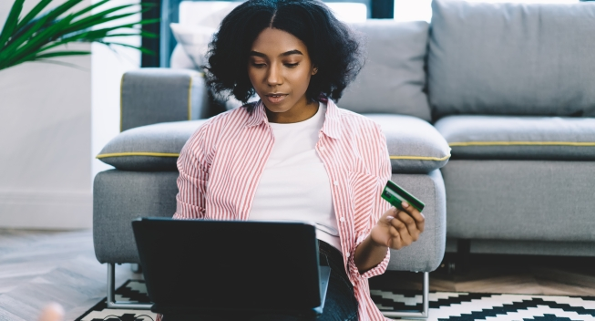 African,American,Young,Woman,With,Credit,Card,In,Hand,Sitting