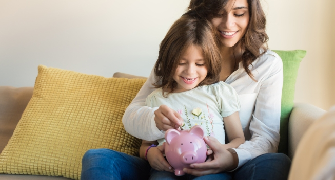 Mother,And,Daughter,Putting,Coins,Into,Piggy,Bank