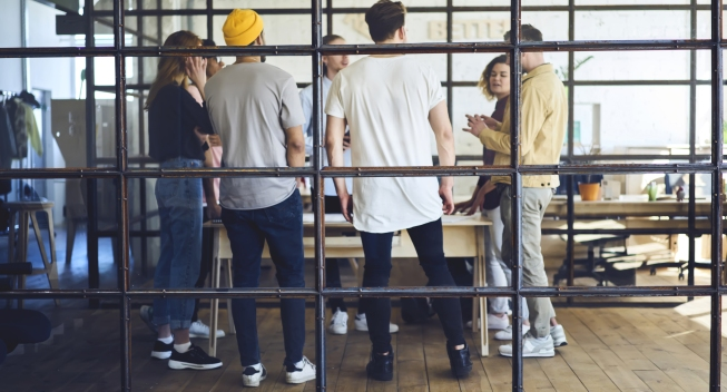 Group,Of,Young,People,Standing,Around,Table,In,Contemporary,Office