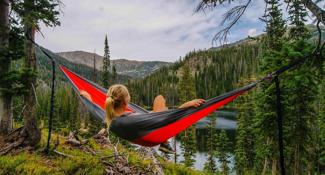 A girl outside on a hammock enjoying the outdoors.