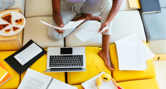 Top view of crop black teenager sitting on couch near laptop and reading documents while doing homework assignment at home