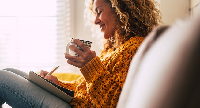 woman journaling with coffee
