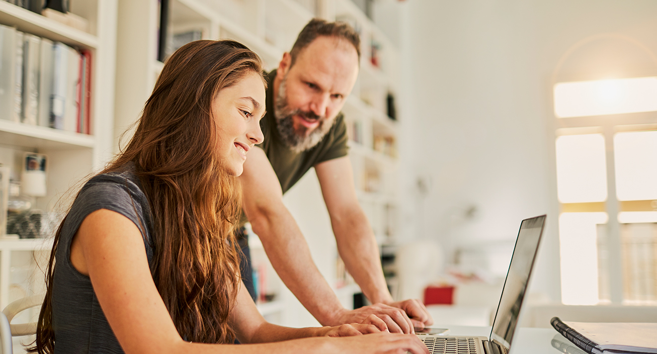 Image of dad and daughter looking at a laptop and laughing together