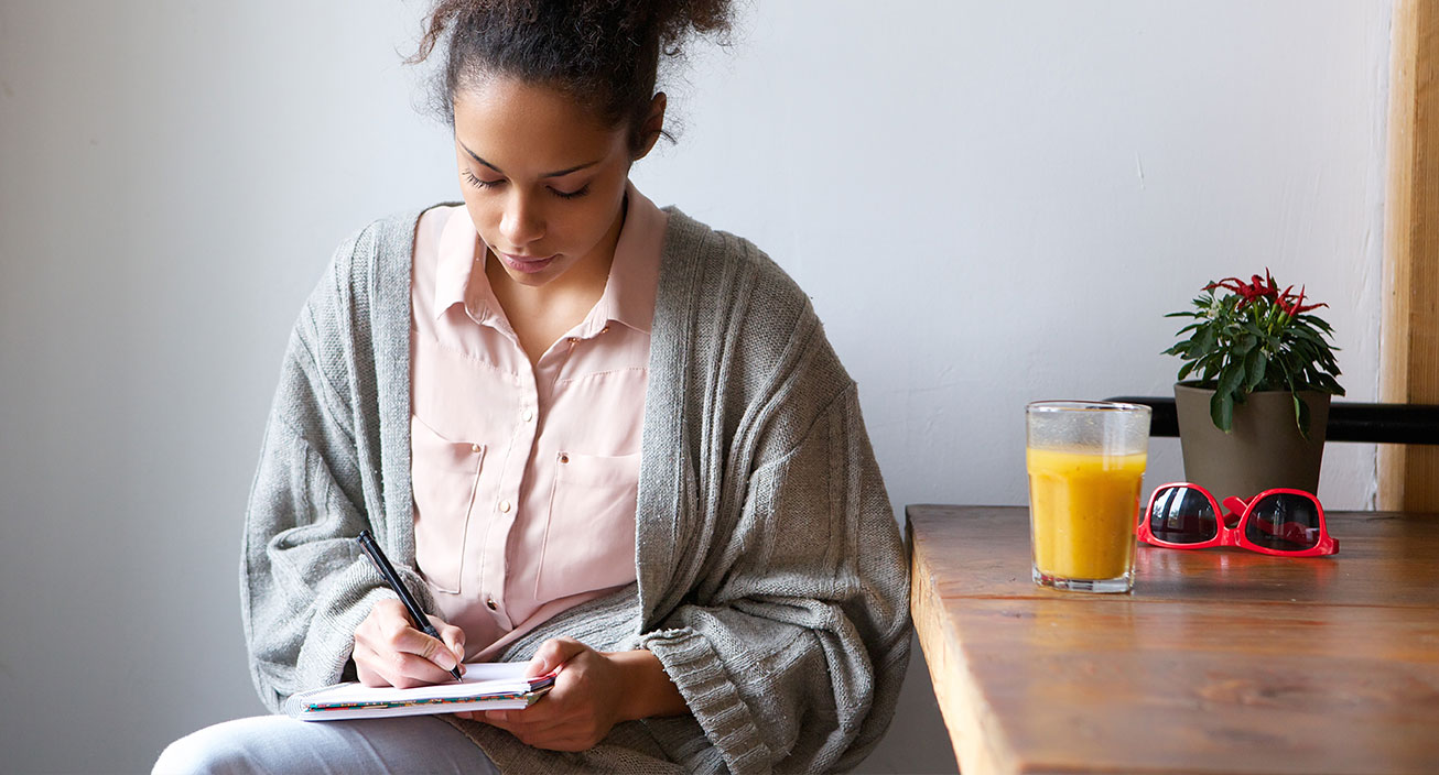 Young woman sitting at home writing on note pad