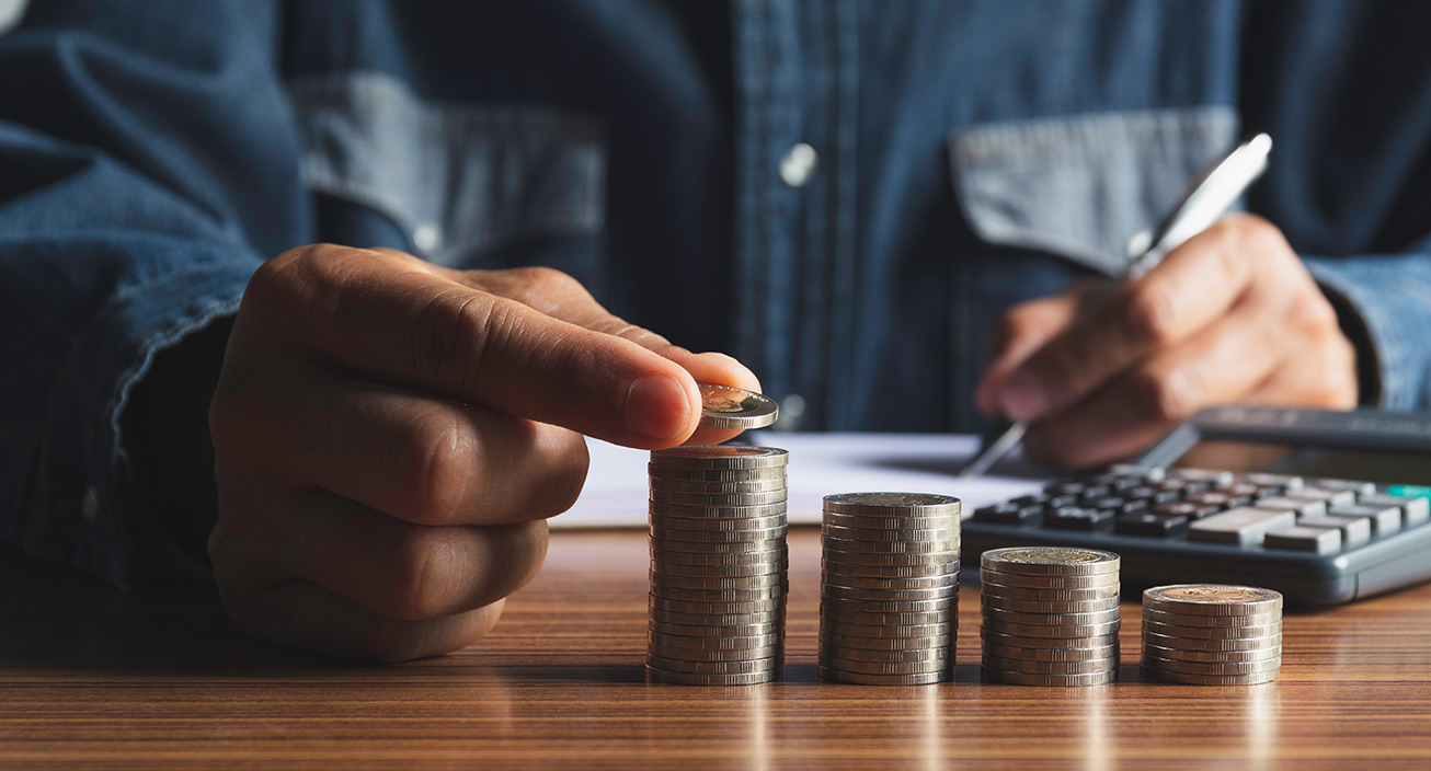 A man counts coins on the table.