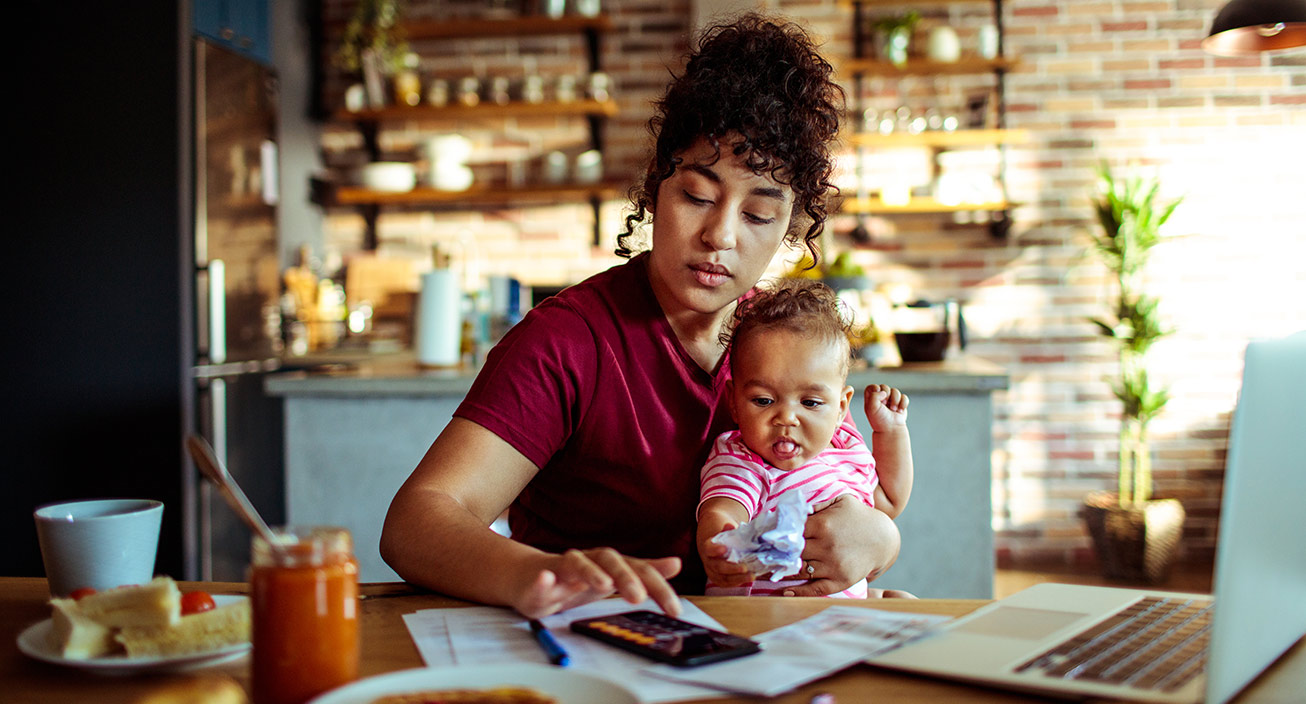 A woman pays the bills with her baby on her lap.