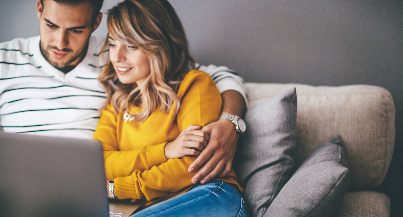 couple relaxing on couch looking at laptop in apartment