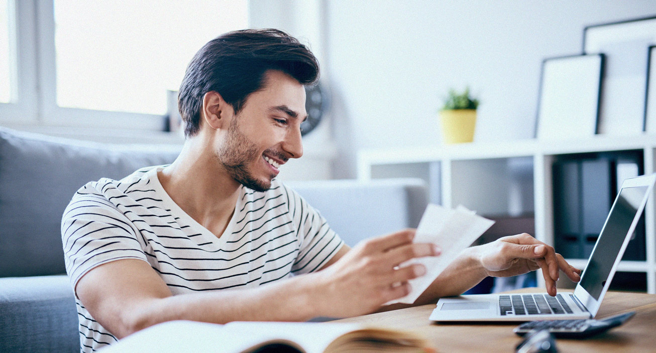 Man with laptop looking at money order