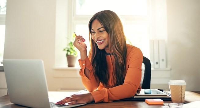 Woman sitting at laptop smiling