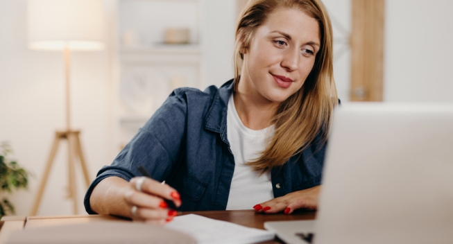 Woman taking notes and looking at laptop