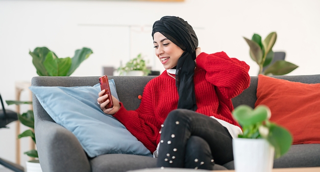Woman In Hijab Smiling and FaceTiming on her Phone