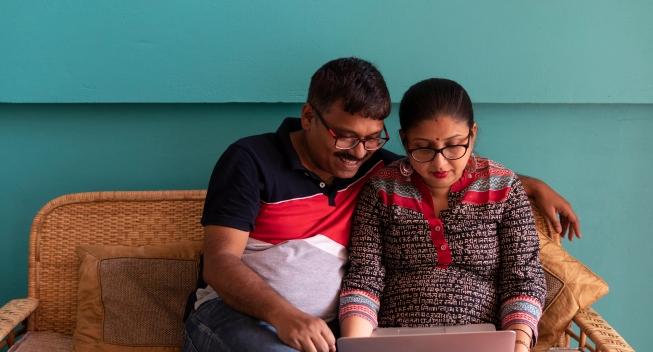 Indian Couple With Laptop Inside Room
