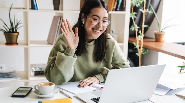 woman-smiling-and-waving-to-video-call-on-laptop