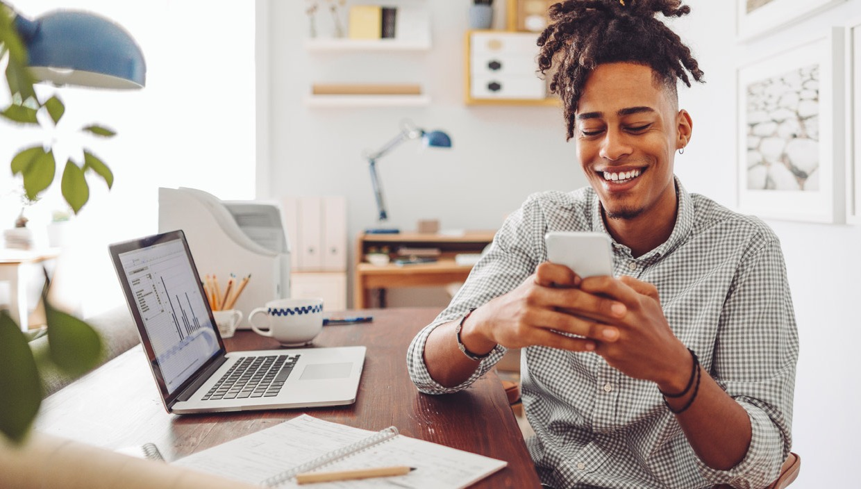 man-happy-phone-investing-home