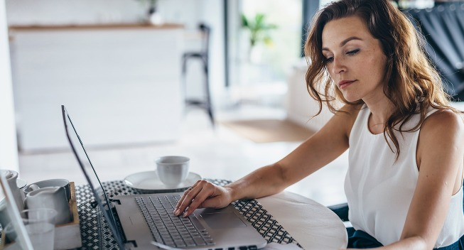 woman-working-at-computer-looking-at-finances