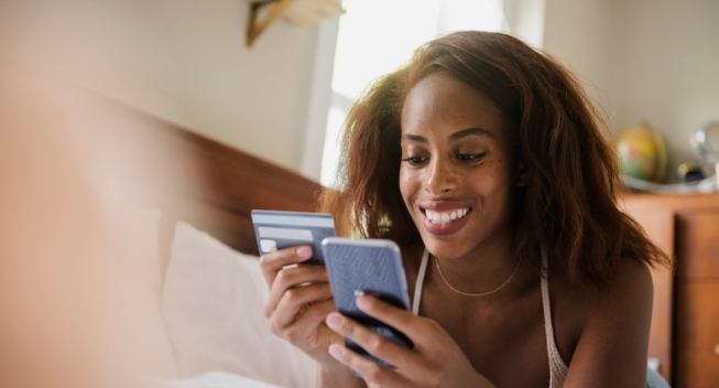 Woman using credit card with smart phone