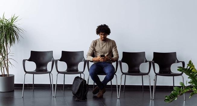 man-sitting-waiting-room-using-phone