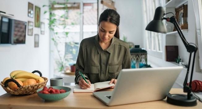 woman-freelancer-writing-notes-laptop